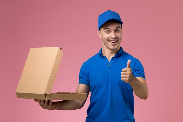 Front view male courier in blue uniform holding food box smiling on the pink wall, job worker uniform service delivery