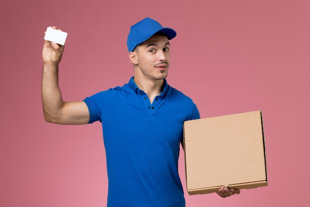 Front view male courier in blue uniform holding food box with card on the pink wall, worker uniform service delivery