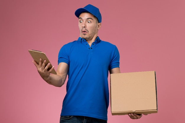 Front view male courier in blue uniform holding food box with notepad on the pink wall, worker uniform service delivery