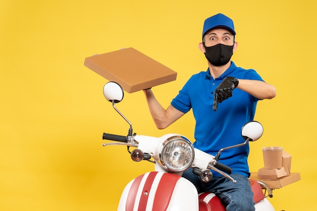 Front view male courier in blue uniform holding food box on yellow virus pandemic covid- delivery service job bike