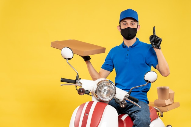 Front view male courier in blue uniform holding food box on yellow virus pandemic covid- delivery work job bike