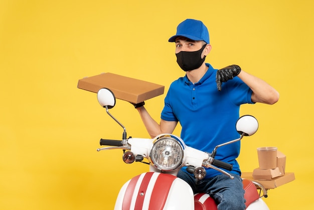 Front view male courier in blue uniform holding food box on a yellow virus pandemic covid- delivery work service job bike