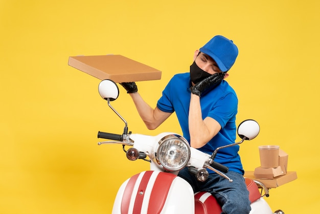 Front view male courier in blue uniform holding food box on the yellow virus pandemic covid- delivery work service job bike