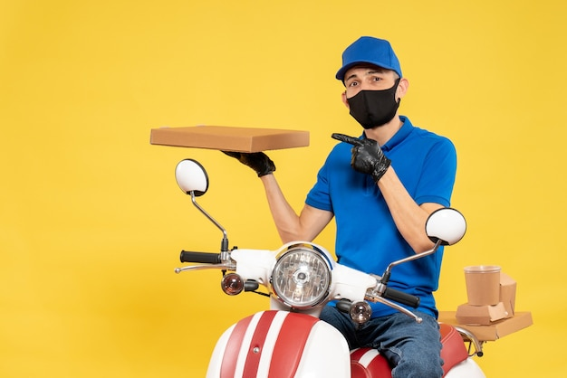Front view male courier in blue uniform holding food box on yellow virus pandemic covid- delivery work service job bike