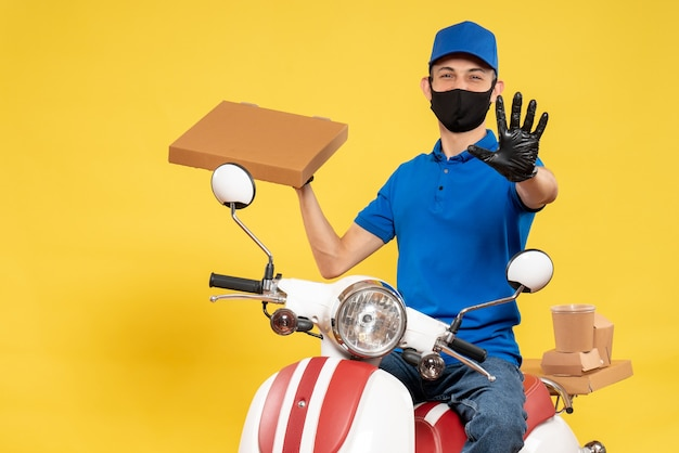 Front view male courier in blue uniform holding food box on yellow virus pandemic covid delivery work service job bike