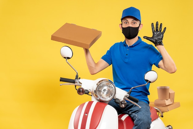 Front view male courier in blue uniform holding food box on yellow virus pandemic covid- delivery work service job