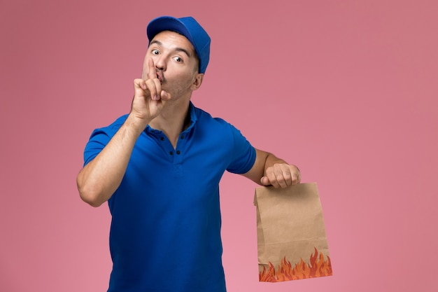 Front view male courier in blue uniform holding food package asking to be silent on pink wall, job worker uniform service delivery