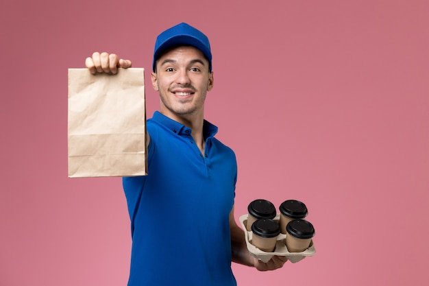 Front view male courier in blue uniform holding food package coffee on pink wall, worker uniform service delivery