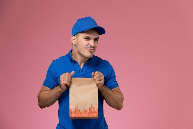 Corriere maschio vista frontale in uniforme blu che tiene il pacchetto alimentare con espressione divertente sul muro rosa, consegna del lavoro di servizio uniforme