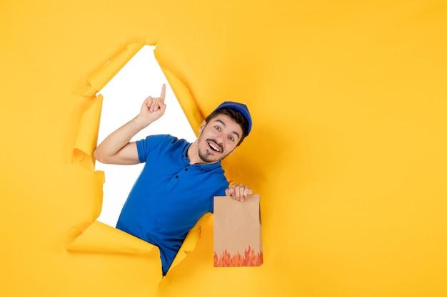 Corriere maschio di vista frontale in uniforme blu che tiene pacchetto di cibo su spazio giallo