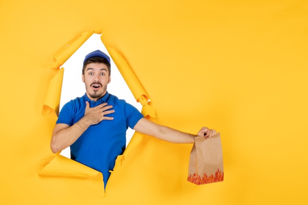 Front view male courier in blue uniform holding food package on yellow space