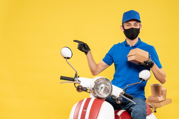 Front view male courier in blue uniform holding little food package on a yellow virus pandemic covid delivery work service job bike