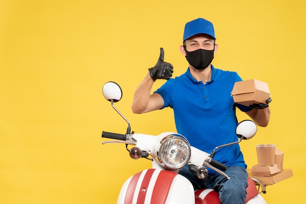 Front view male courier in blue uniform holding little food package on the yellow virus pandemic covid delivery work service job bike