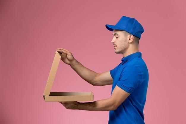 Corriere maschio di vista frontale in uniforme blu che tiene la scatola di consegna del cibo di apertura sulla parete rosa, consegna di lavoro di servizio uniforme