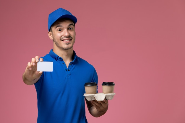Front view male courier in blue uniform holding white card coffee cups with smile on pink wall, job worker uniform service delivery