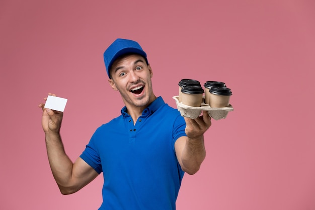 Front view male courier in blue uniform holding white card and delivery coffee cups on pink wall, uniform job worker service delivery