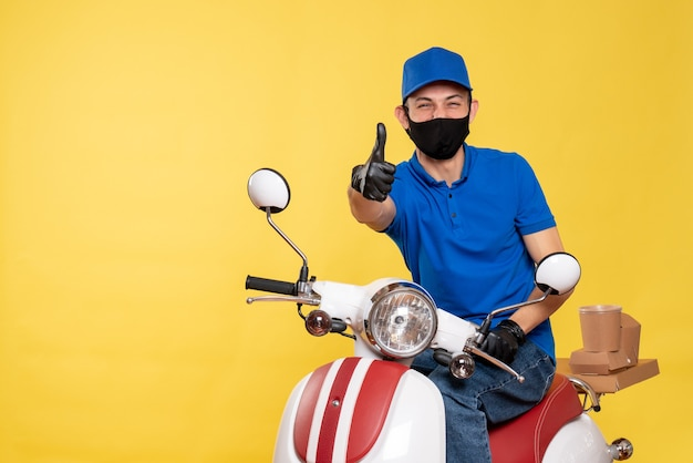 Front view male courier in blue uniform and mask laughing on yellow job bike covid- pandemic delivery virus service work