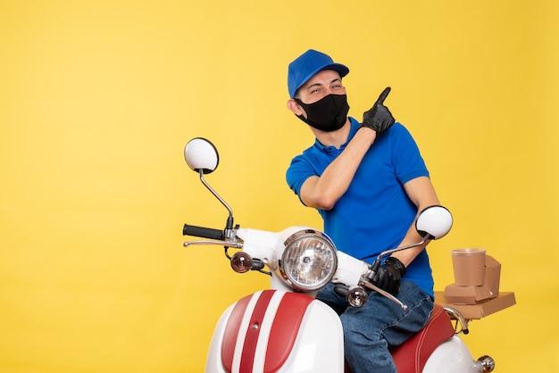 Corriere maschio di vista frontale in uniforme blu e maschera che ride sulla bici di virus di lavoro di servizio di pandemia di lavoro di covid-consegna gialla