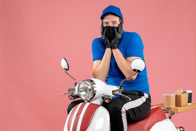Corriere maschio vista frontale in uniforme blu e maschera su cibo rosa servizio di fast-food lavoro in bici lavoro di consegna covid