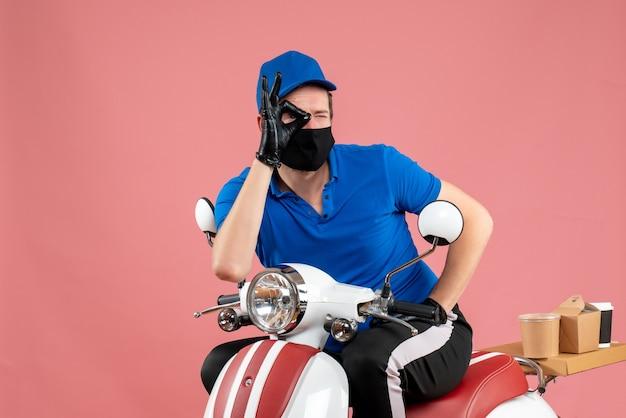 Corriere maschio vista frontale in uniforme blu e maschera sul lavoro rosa servizio di fast-food lavoro in bicicletta covid- virus alimentare