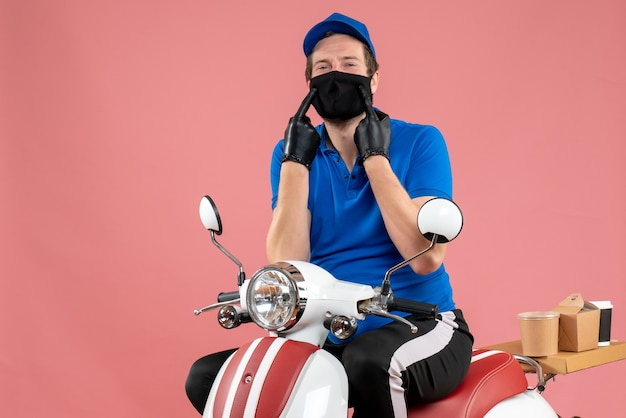 Corriere maschio vista frontale in uniforme blu e maschera sul servizio rosa fast-food covid- lavoro virus bici