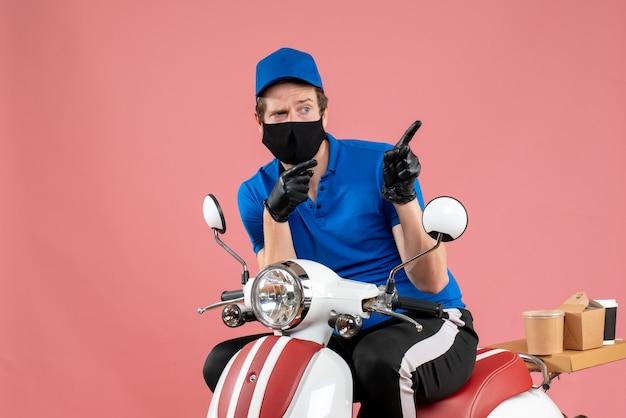 Corriere maschio vista frontale in uniforme blu e maschera su lavoro in bici virus rosa fast-food servizio covid lavoro