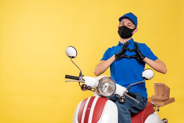 Corriere maschio di vista frontale in uniforme blu e maschera che invia amore sulla bici di pandemia di lavoro di servizio di consegna di covid di lavoro di virus giallo