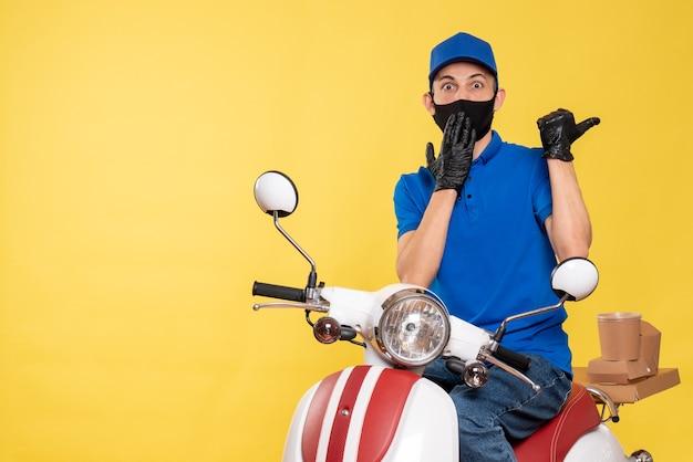 Corriere maschio di vista frontale in uniforme blu e maschera sul virus del lavoro di servizio della bici di consegna del covid del lavoro giallo