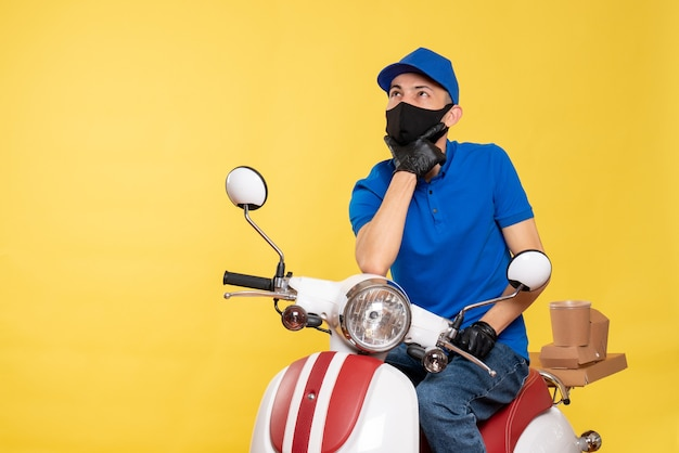 Front view male courier in blue uniform and mask on a yellow work covid- pandemic service job virus bike delivery