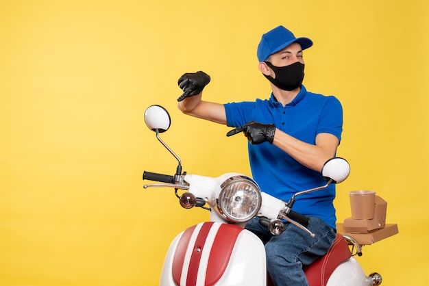 Front view male courier in blue uniform and mask on the yellow work covid- pandemic service job virus bike delivery
