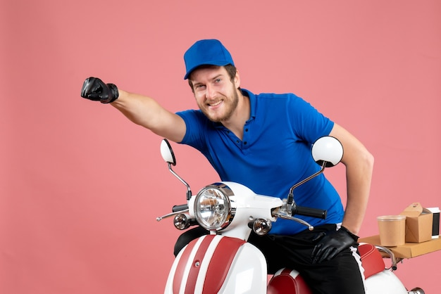 Front view male courier in blue uniform on a pink work delivery fast-food job service color bike