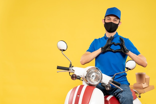 Front view male courier in blue uniform sending love on yellow delivery virus covid- service job bike pandemic work