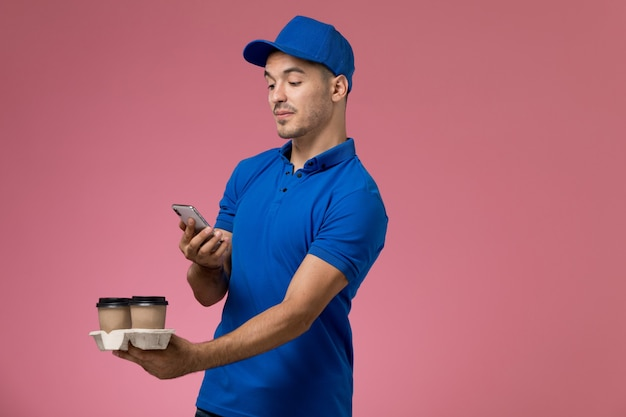 Corriere maschio di vista frontale in uniforme blu che prende una foto del caffè sulla parete rosa, consegna di servizio uniforme del lavoratore