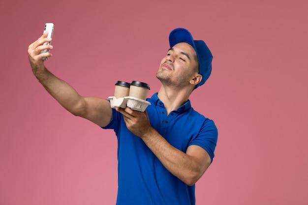 Corriere maschio di vista frontale in uniforme blu che prende un selfie con le tazze di caffè sulla parete rosa, consegna di servizio uniforme del lavoratore