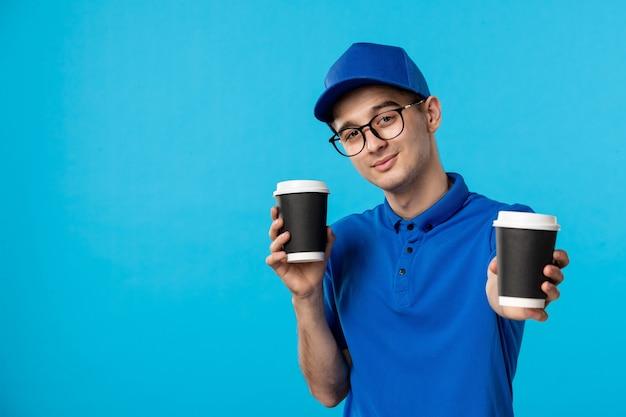Vista frontale del corriere maschio in uniforme blu con caffè sull'azzurro