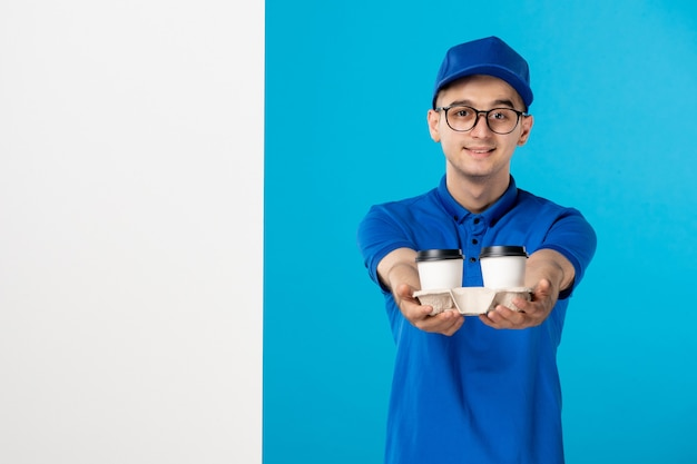 Front view male courier in blue uniform with coffee on a blue