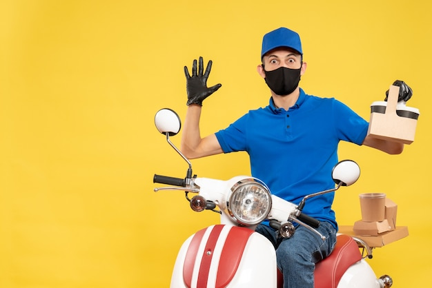 Front view male courier in blue uniform with coffee on yellow pandemic bike covid- job delivery virus service