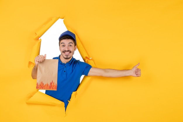 Front view male courier in blue uniform with food package on the yellow space