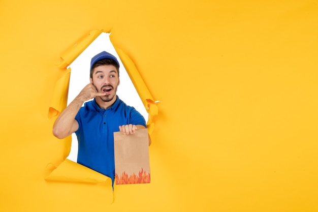 Front view male courier in blue uniform with food package on yellow space