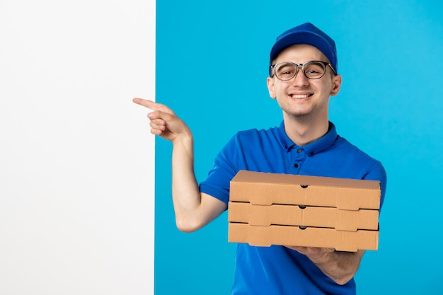 Vista frontale del corriere maschio in uniforme blu con pizza sul blu