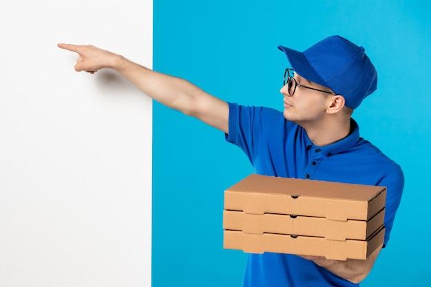 Vista frontale del corriere maschio in uniforme blu con scatole per pizza sul blu