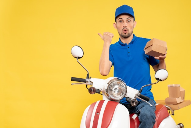 Front view male courier in blue uniform on yellow delivery worker service bike work uniform