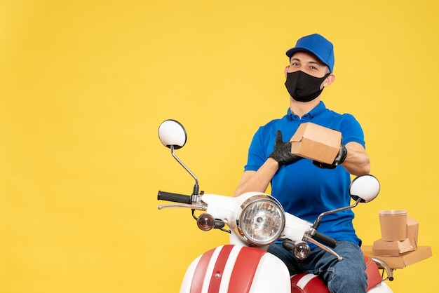Front view male courier in blue uniform on yellow job delivery virus covid- service bike pandemic work food