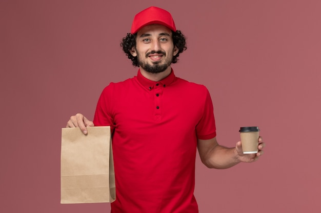 明るいピンクの壁のサービス配達従業員に茶色のコーヒーカップと食品パッケージを保持している赤いシャツとケープの正面図男性宅配便配達人