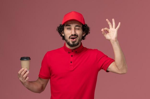 淡いピンクの壁に茶色のコーヒーカップを保持している赤いシャツとケープの正面図男性宅配便配達人サービス制服配達従業員の仕事