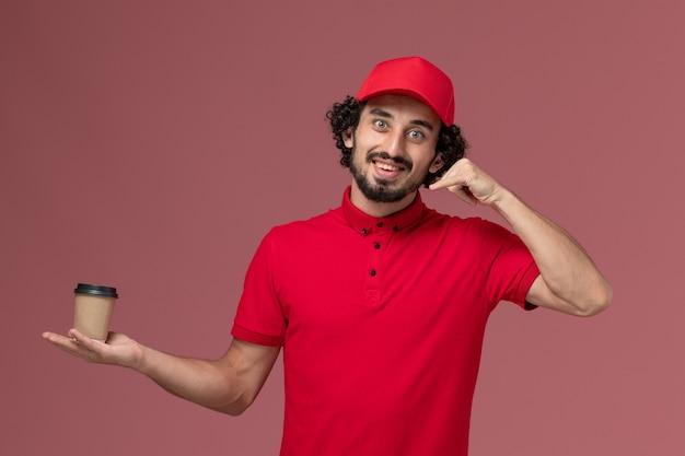 ピンクの壁に茶色のコーヒーカップを保持している赤いシャツと岬の正面図男性宅配便配達人サービス制服配達従業員労働者