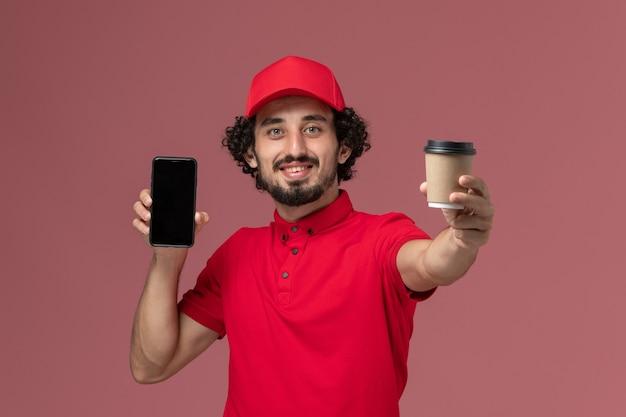 明るいピンクの壁に茶色の配達コーヒーカップと電話を保持している赤いシャツとケープの正面図男性宅配便配達人サービス配達従業員の仕事