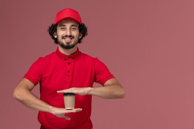 淡いピンクの壁のサービス配達従業員に茶色の配達コーヒーカップを保持している赤いシャツと岬の正面図男性宅配便配達人