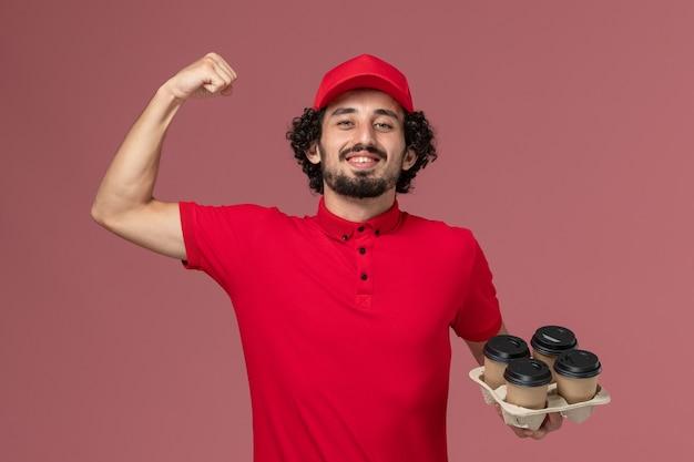 赤いシャツとケープの男性宅配便配達人が茶色の配達コーヒーカップを保持し、淡いピンクの壁のサービス配達従業員を曲げる正面図