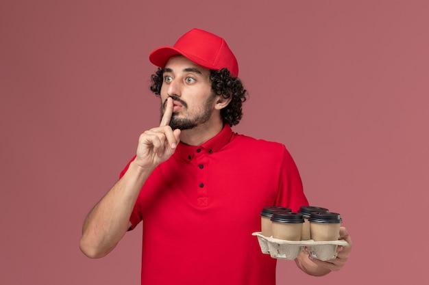 明るいピンクの壁に茶色の配達コーヒーカップを保持している赤いシャツとケープの正面図男性宅配便配達人男性サービス配達従業員の仕事